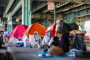 Twitch Napier, who is homeless, sits with her dog, Shiva, near tents set up under the 101 Freeway along Division Street, part of a large homeless encampment, in San Francisco, Feb. 25, 2016. An order by the city's authorities to vacate the sidewalk tent camp in the commercial district has rekindled passions over the city's longstanding homeless problem, which residents say has reached crisis levels. (Gabrielle Lurie/The New York Times)