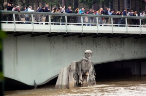People looking at the floods stand on the Alma bridge by the Zouave statue which is used as a measuring instrument during floods in Paris, France Friday June 3, 2016. Both the Louvre and Orsay museums were closed as the Seine, which officials said was at its highest level in nearly 35 years, was expected to peak sometime later Friday. (AP Photo/Jerome Delay)